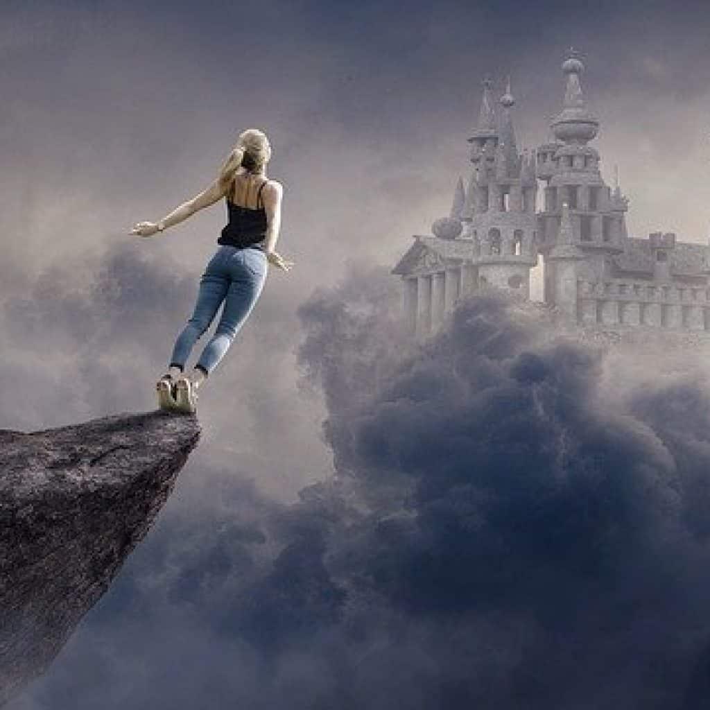 Eine Frau steht auf einem Felsvorsprung und springt ins Ungewisse in Richtung Schloss
