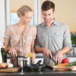 Eine Frau und ein Mann besprechen die Firmenübernahme während der Zubereitung eines Nachtessens.